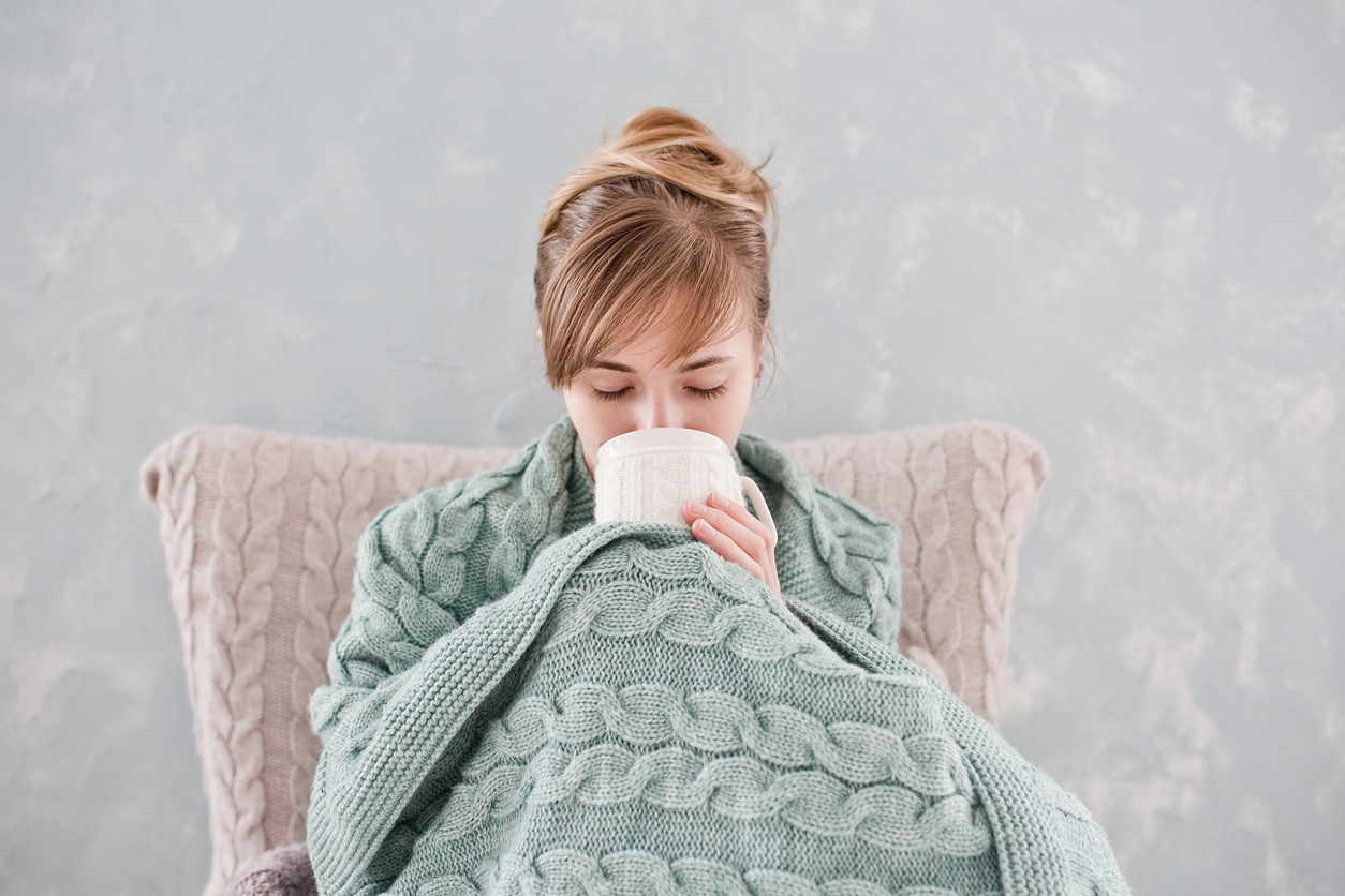 Attractive woman with natural blond hair posing without makeup with white cup of hot drink wrapped with blanket at home